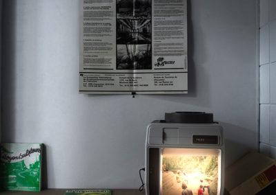 Mathieu Grenier, Symposium, 2015, Bande sonore à 10 canaux, enceintes acoustiques, bande sonore stéréo, casque d'écoute, lettre manuscrite, procuration manuscrite, projecteur Telex caramate 4100, plusieurs documents d'archives privés, boîtes de rangement, Symposium international de sculpture environnementale de Chicoutimi
